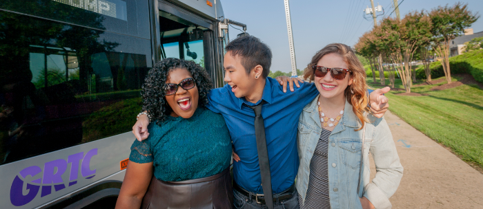 A group of three young people laughing as they walk away from a GRTC bus.